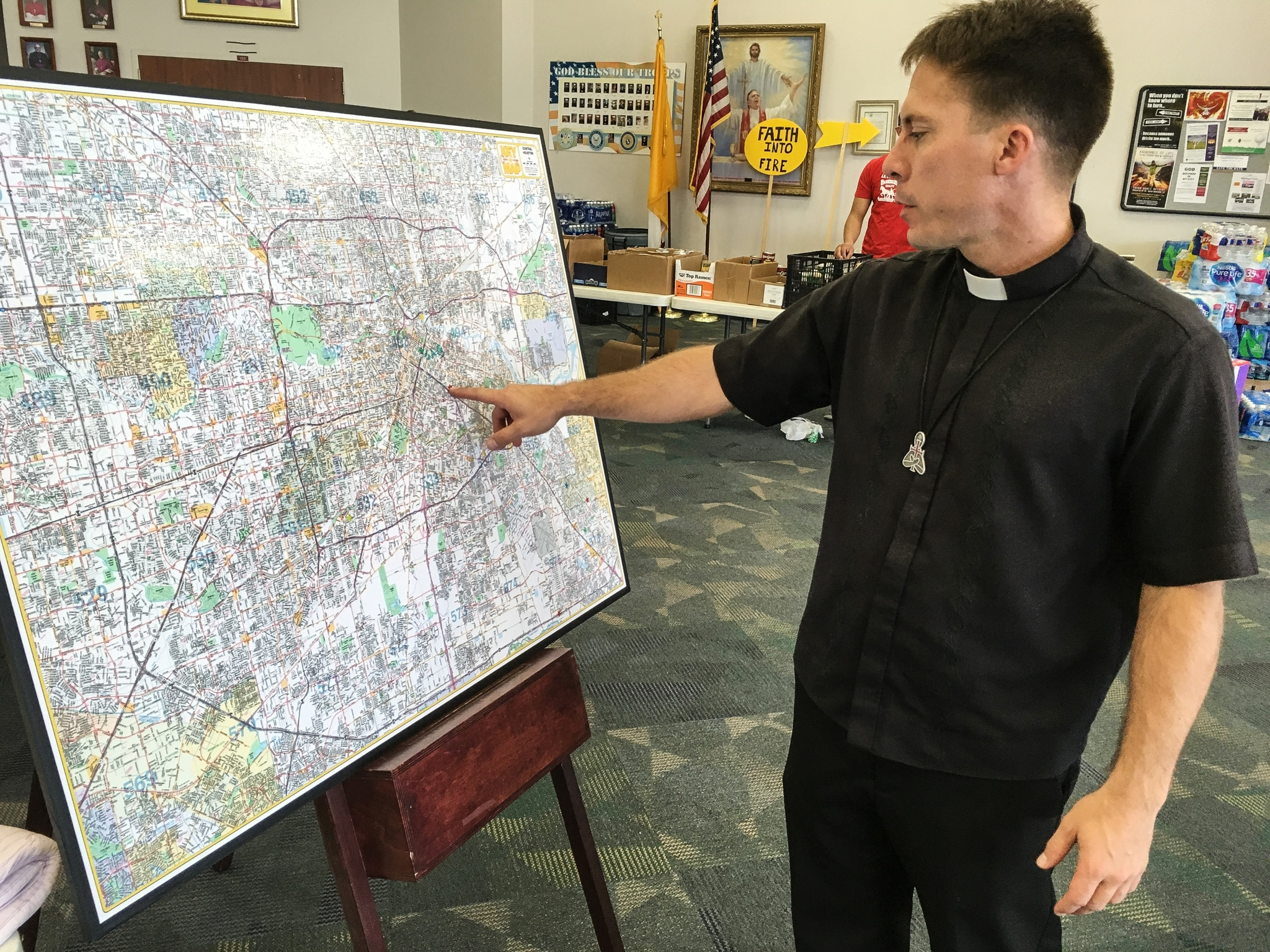 Man in clerical collar pointing to a map (© AP Images)