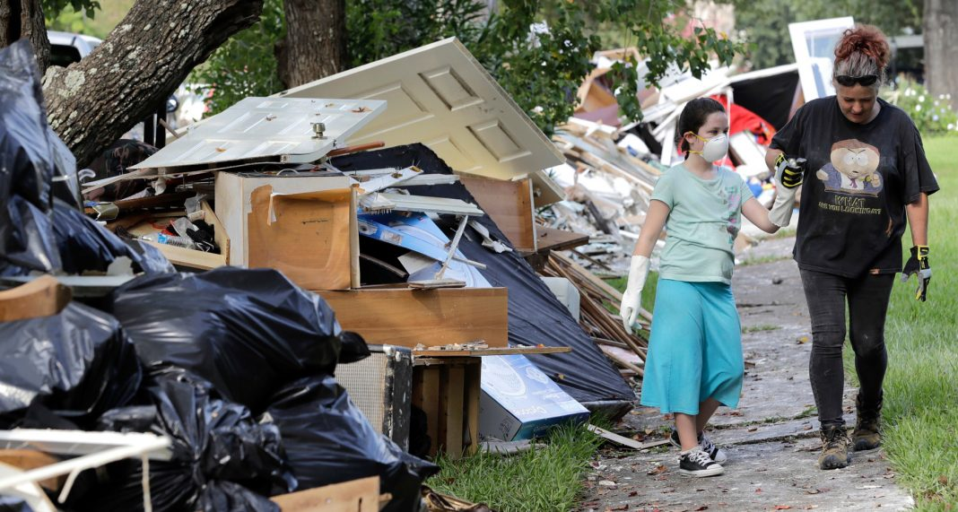 Woman holding hands with child as they pass debris piled on lawns (© AP Images)