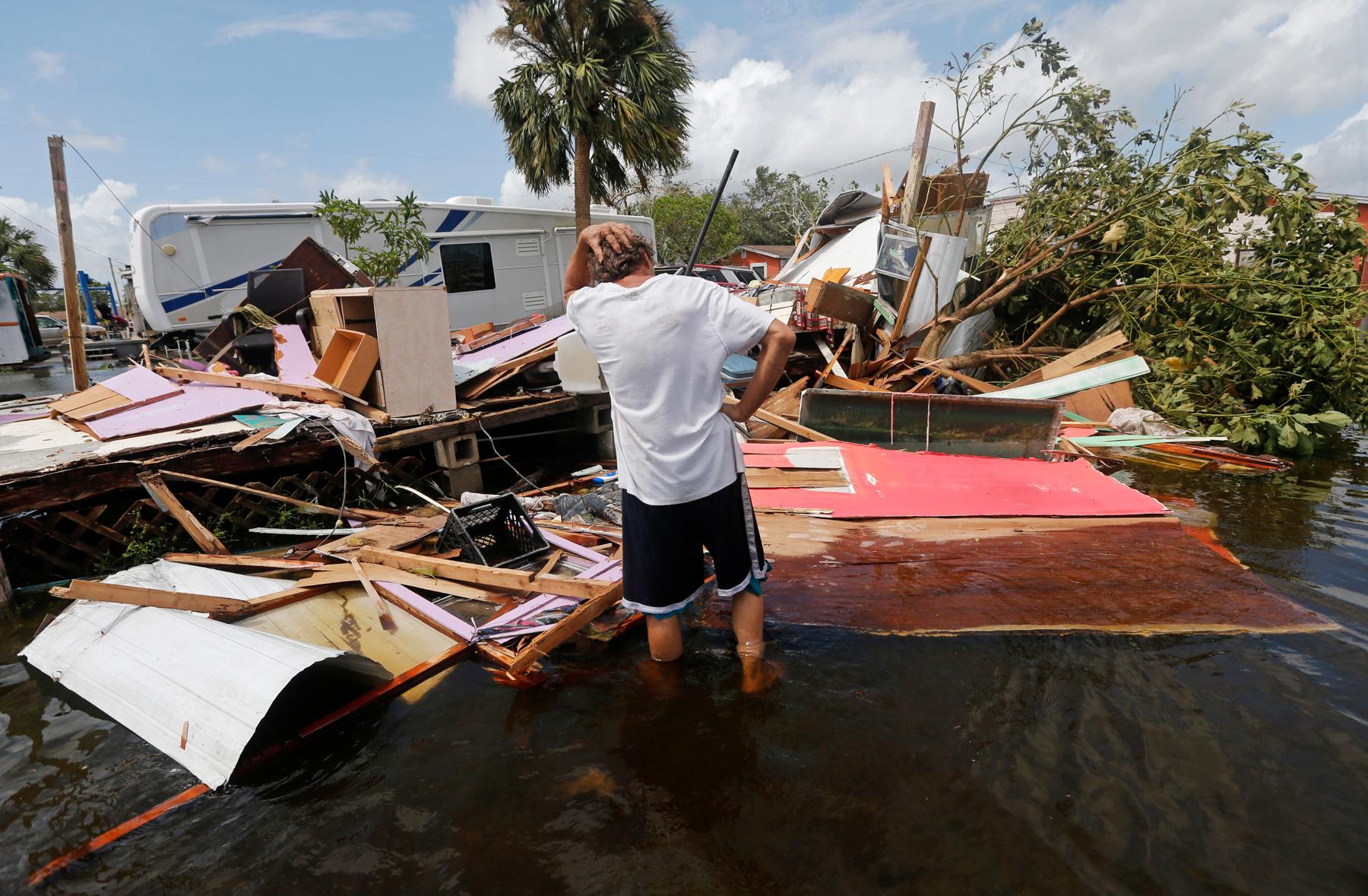 Man standing in water and surveying piles of debris (© Gerald Herbert/AP Images)