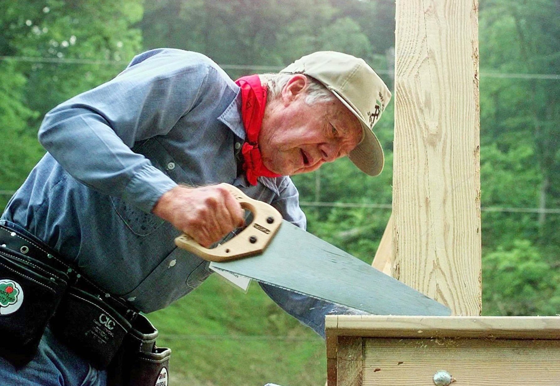 Jimmy Carter sawing plywood (© AP Images)