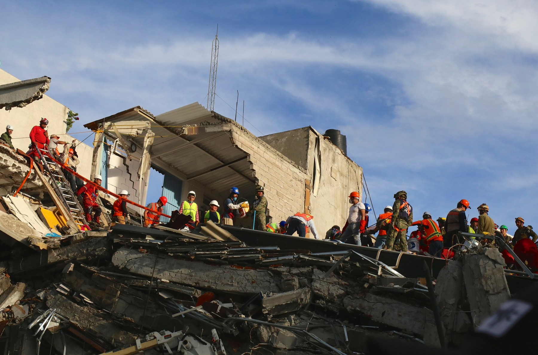 People wearing safety gear standing amid rubble and broken buildings (USAID Office of U.S. Foreign Disaster Assistance)
