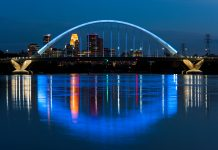 Illuminated bridge over reflective water against a skyline (© Joe Mamer Photography/Alamy Stock Photo)