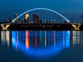 Illuminated bridge over reflective water against a skyline (© Joe Mamer Photography/Alamy Stock Photo)