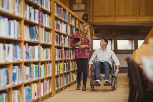 Студент в коляске в библиотеке (© Wavebreak Media ltd/Alamy Stock)