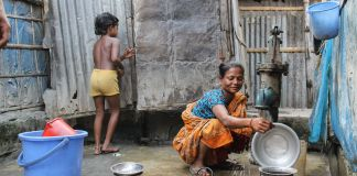 Child and woman in small courtyard with water pump (© Raveena Aulakh/Toronto Star/Getty Images)