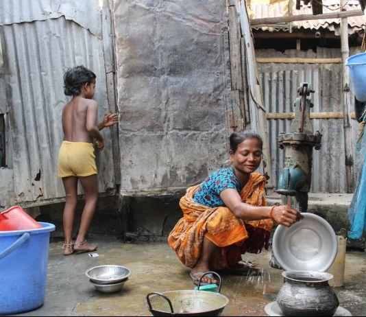 Criança e mulher em pequeno pátio com bomba d'água (© Raveena Aulakh/Toronto Star/Getty Images)
