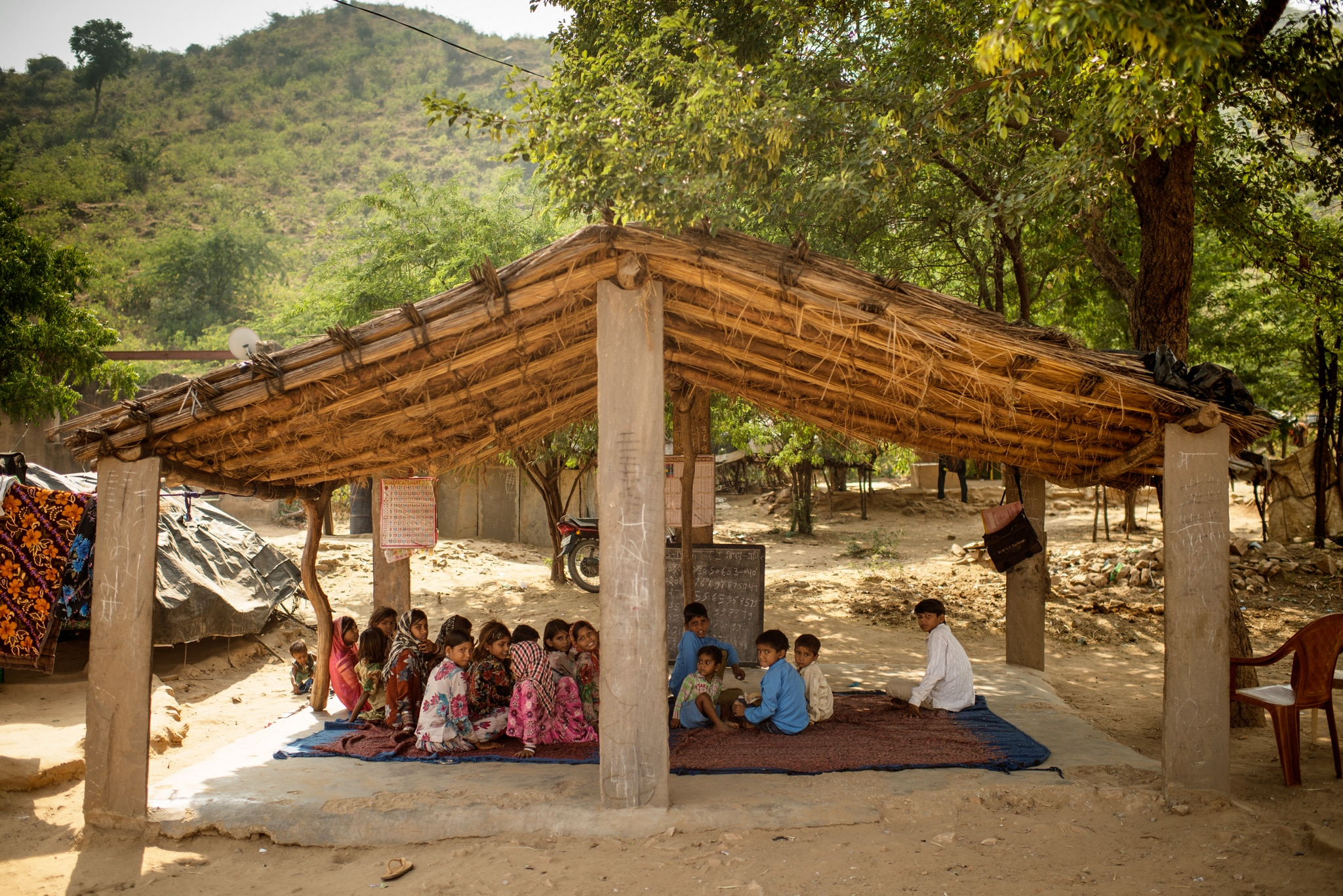 Crianças sentadas em tapete sob estrutura improvisada (© Jonas Gratzer/LightRocket/Getty Images)