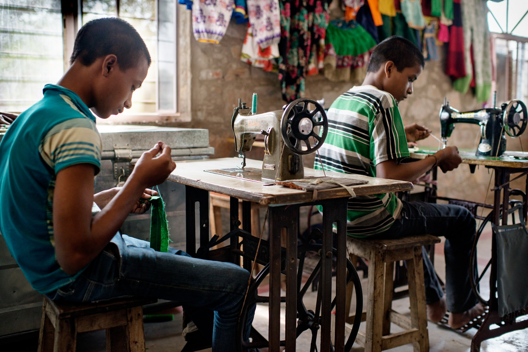 Two boys working at sewing machines (© Jonas Gratzer/LightRocket via Getty Images)