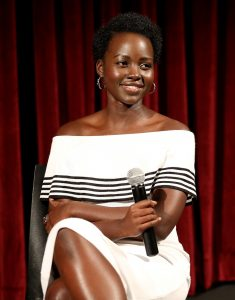 Lupita Nyong'o in white dress holding microphone (© Robin Marchant/Getty Images)