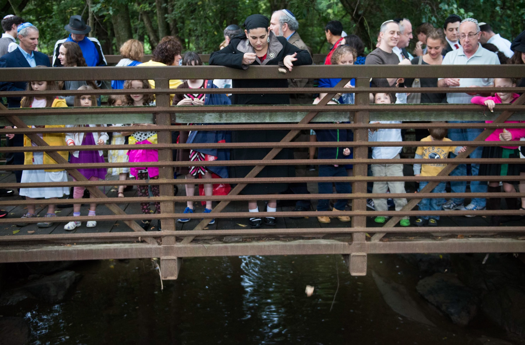 Crowd of people on a bridge dropping bread into creek below (© Linda Davidson/Washington Post via Getty Images)