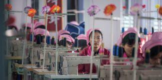 Mulheres sentadas em máquinas de costura em uma fábrica (© Ed Jones/AFP/Getty Images)