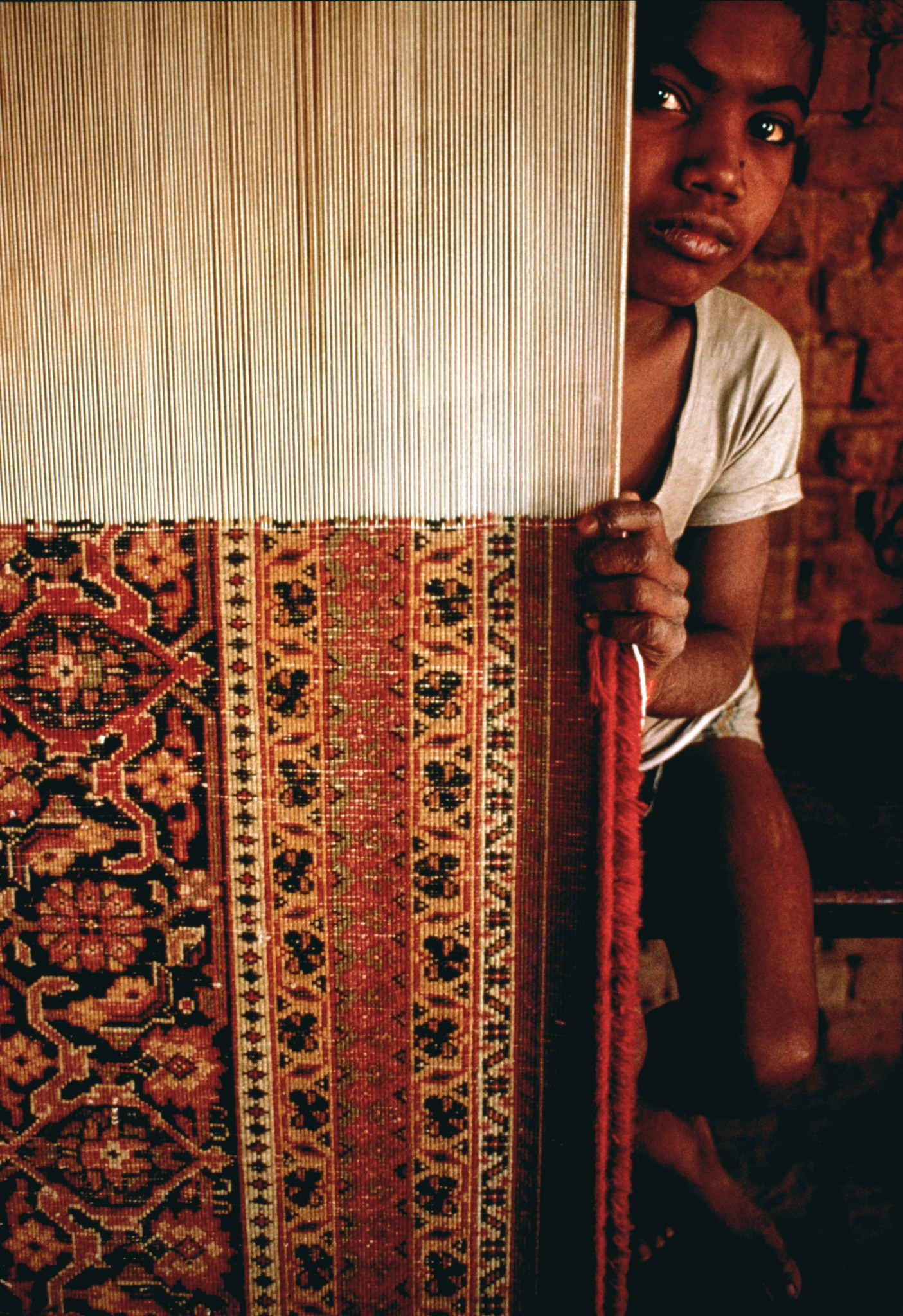 Child peering out from behind rug on loom (© Tom Stoddart/Getty Images)
