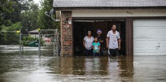 People standing in garage in floodwaters (© Joe Raedle/Getty Images)