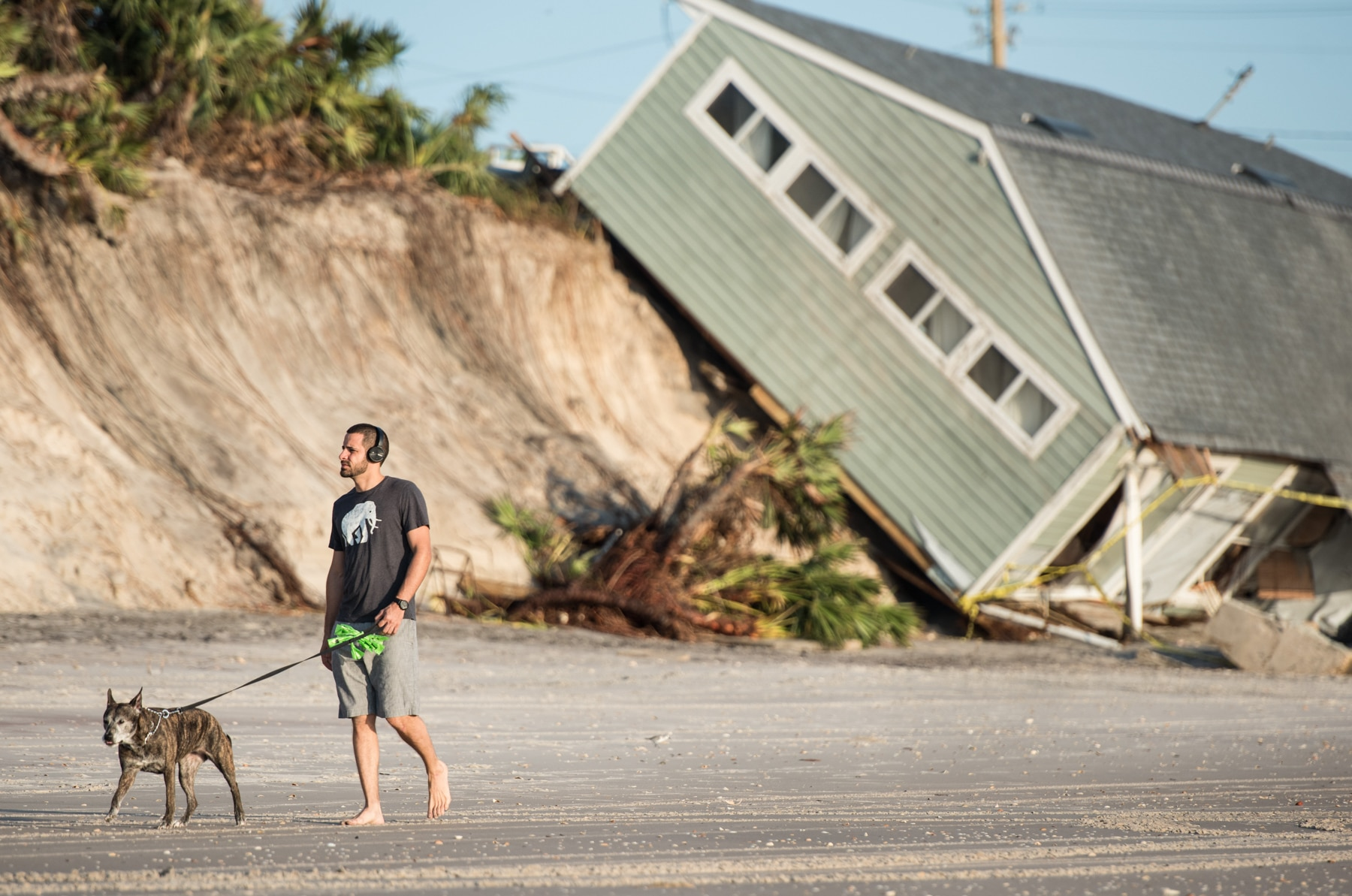 Man walking dog past house that slid down hill (© Sean Rayford/Getty Images)