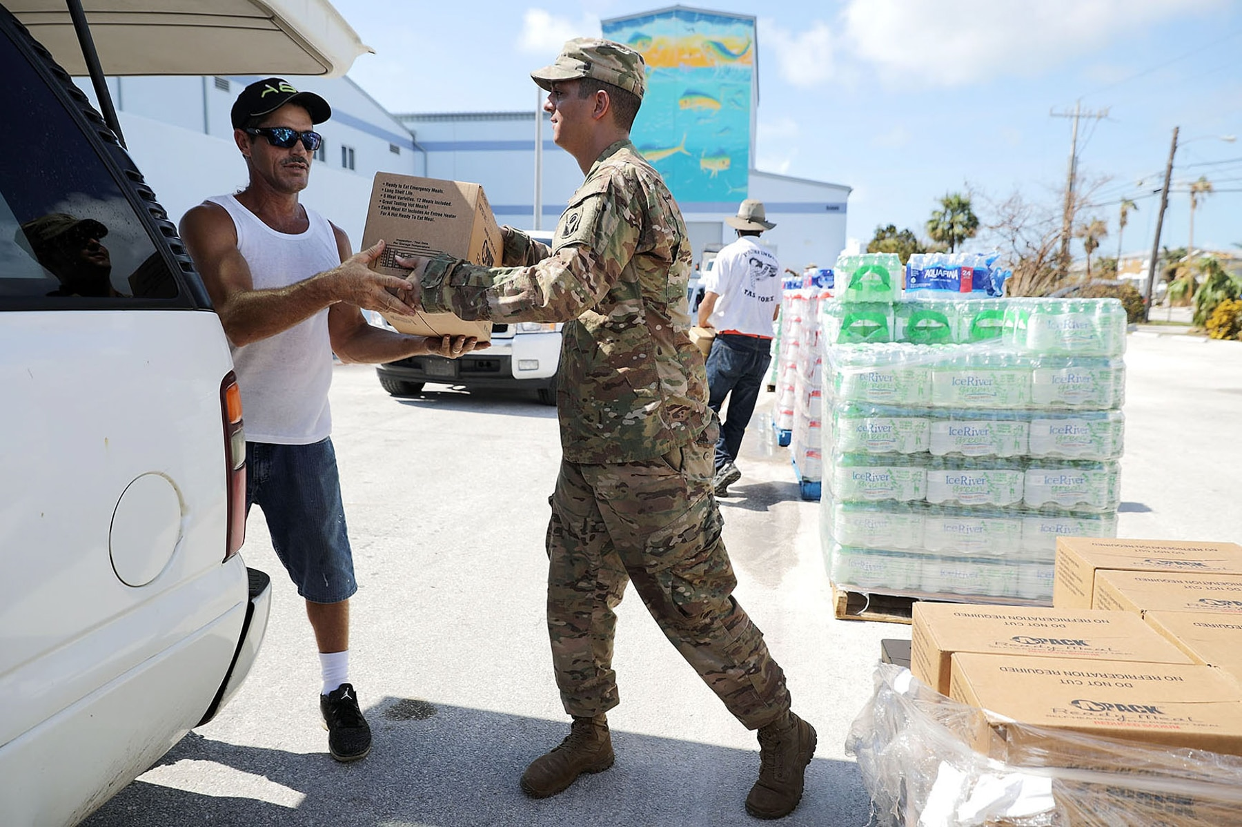 Man receiving box of supplies from soldier to load in his car (Chip Somodevilla/Getty Images)