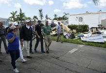 President Trump surveying hurricane damage with group of people (© Brendan Smialowski/AFP via Getty Images)
