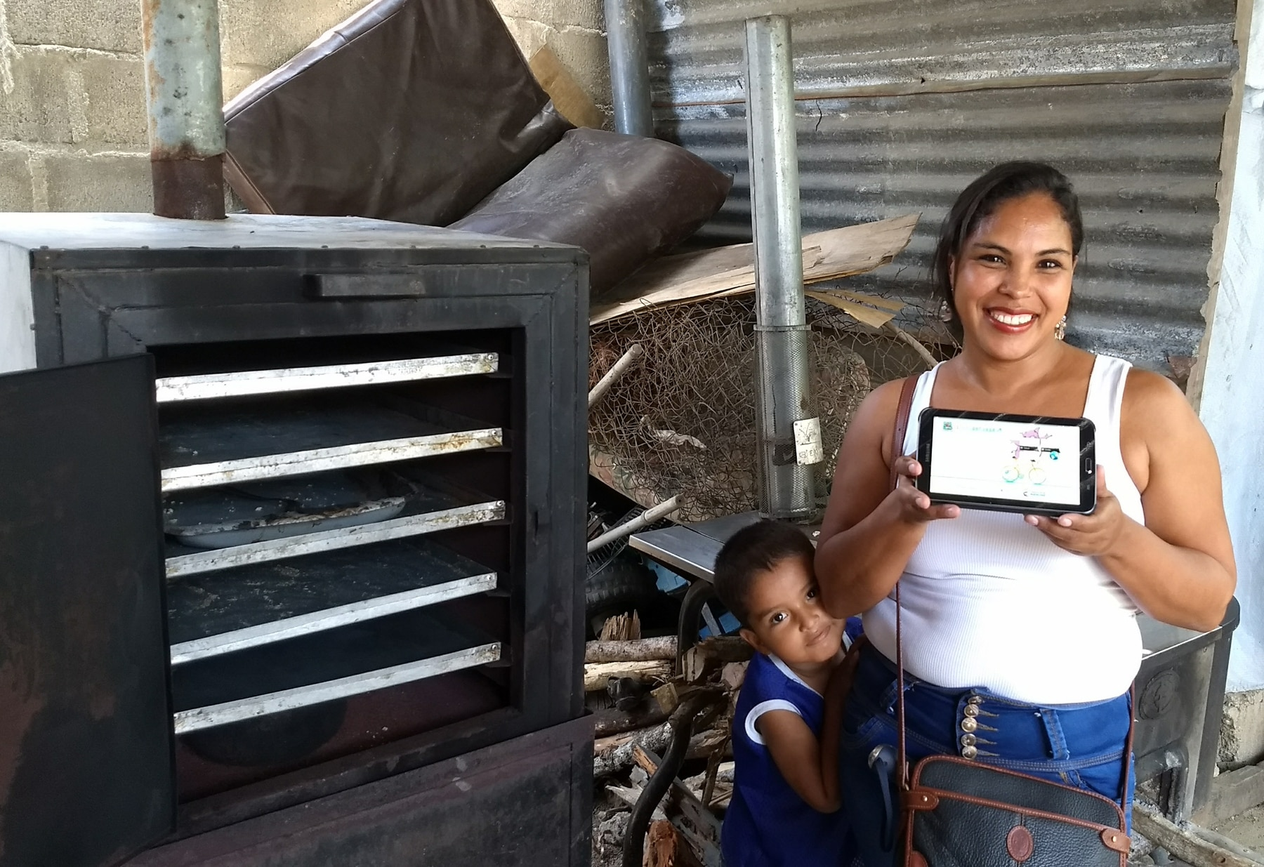 Woman holding electronic tablet and standing next to oven (Fundación Capital)