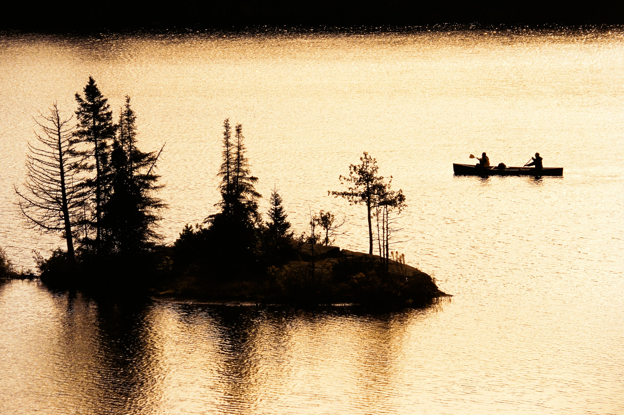 People canoeing on water near small island (© Paul Chesley/National Geographic Creative)