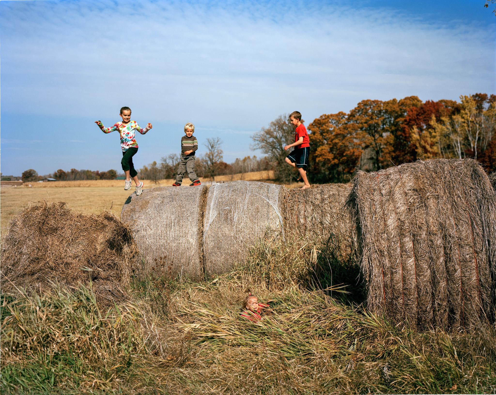 Children playing on large bales of hay in field (© Erika Larsen)