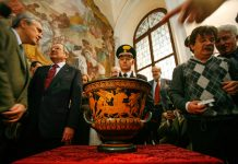People standing around ornate vase on table (© Dario Pignatelli/Reuters)