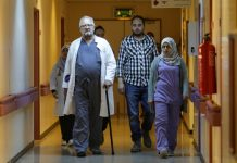 A doctor with a cane and other people walking down a hospital corridor (© Esam Omran Al-Fetori/Reuters)