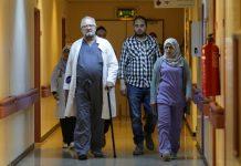Médico com bengala e outras pessoas caminham em corredor de hospital (© Esam Omran Al-Fetori/Reuters)