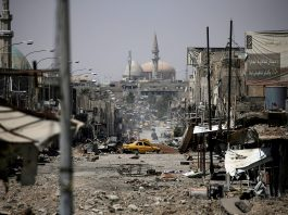 Destroyed street with taxi and mosque in distance (© Alkis Konstantinidis/Reuters)