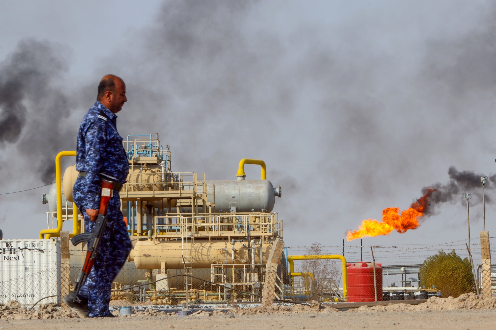 Police officer with rifle walking past oil processing structure and flaming oil well (© Essam Al-Sudani/Reuters)