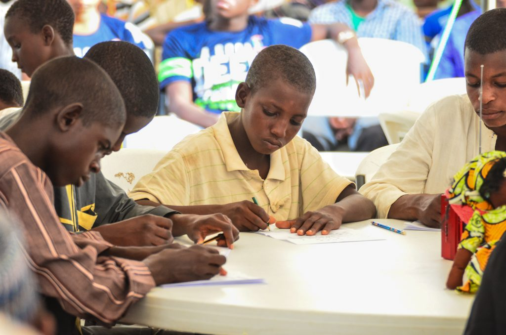Boys sitting at a table writing (© American University of Nigeria)