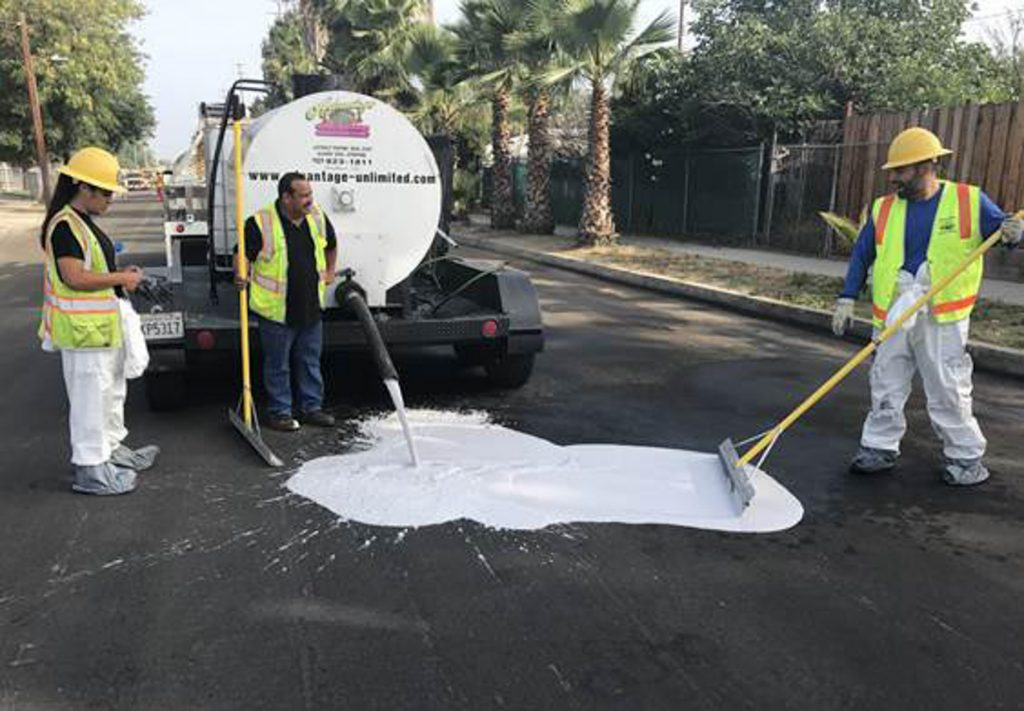 Two people in safety gear standing as a third spreads white liquid spilling from truck onto blacktop (Los Angeles Bureau of Street Services)