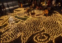 Lit oil lamps arranged in a pattern on the ground (Shutterstock)