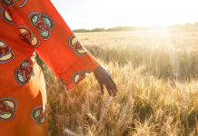 Woman in colorful dress walking in a wheat field (Shutterstock)