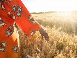 Mulher com vestido colorido caminha por um campo de trigo (Shutterstock)