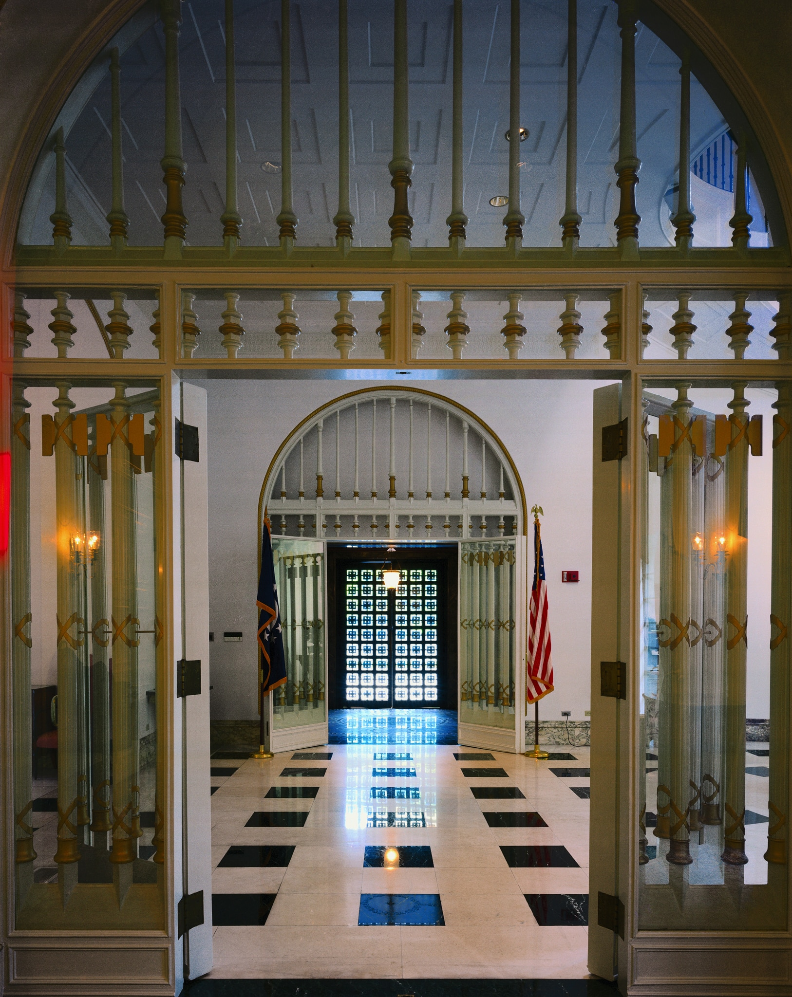 Entryway with glass-enclosed bronze columns, large tiled floor and lattice of glass panels at end of hall (State Dept.)