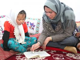 Woman and young girl looking at book (© UNICEF Afghanistan/2016/Sheida)