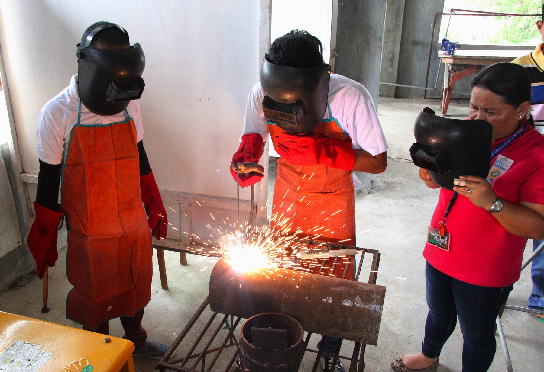 Two people watching as a third welds (Leoncio M. Rodaje for USAID)