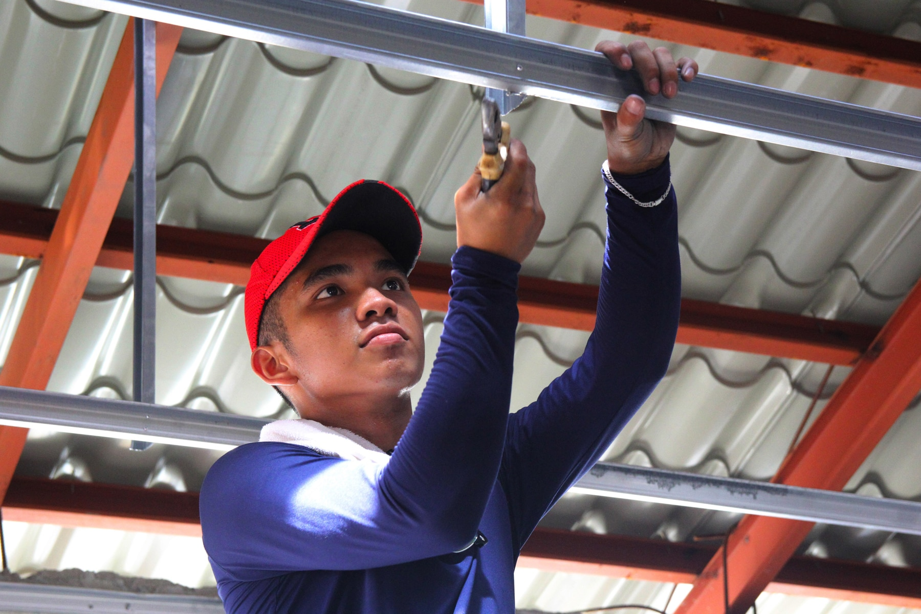 Man securing rivets in ceiling joists (Leoncio M. Rodaje for USAID)