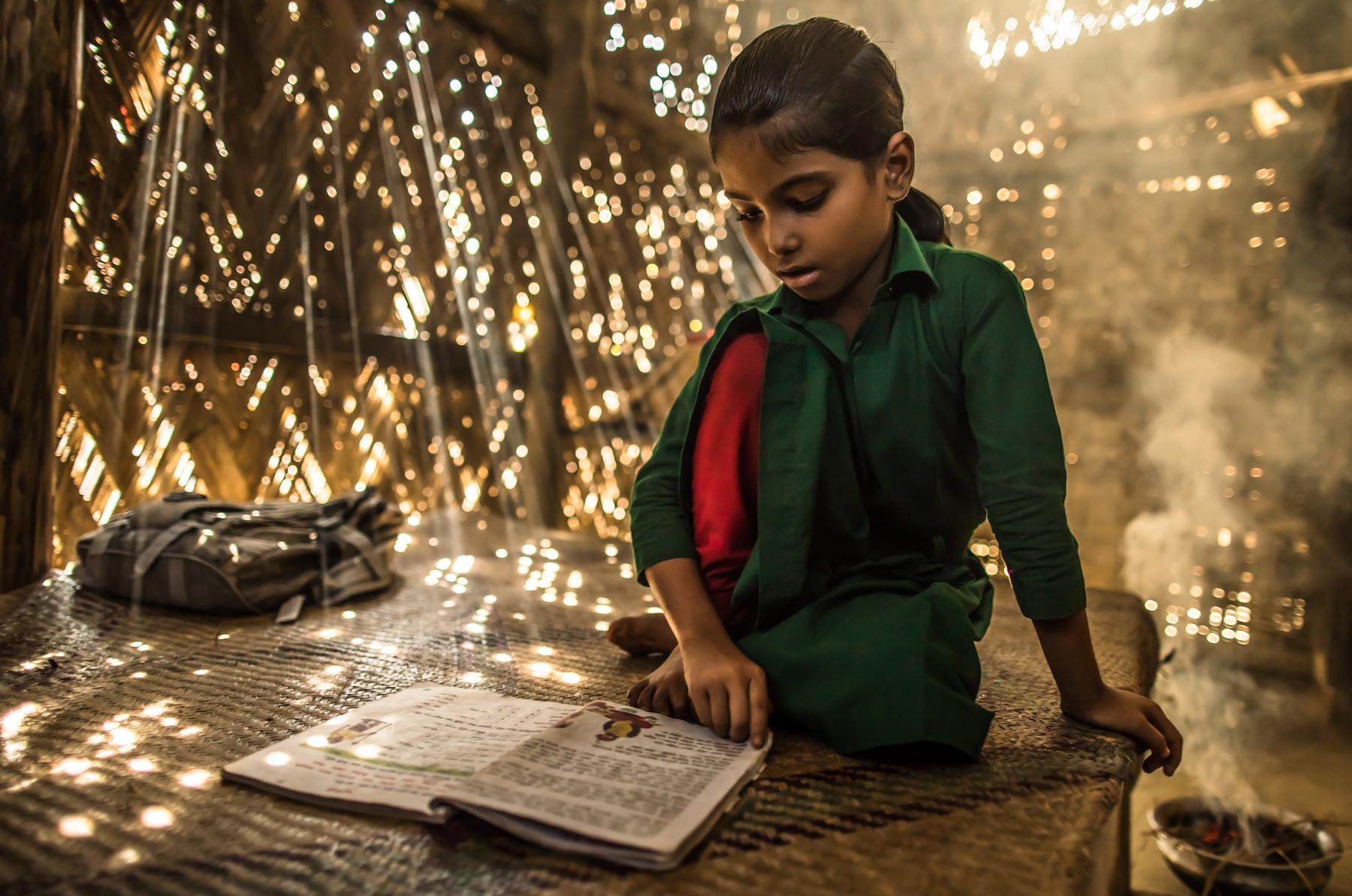 Girl studying with book (USAID/Morgana Wingard)