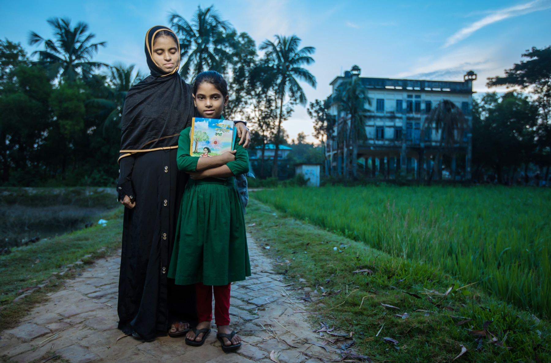 Mother and daughter standing on walkway, daughter holding book (USAID/Morgana Wingard)