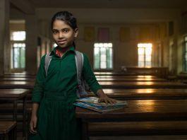 Girl standing in empty classroom (USAID/Morgana Wingard)