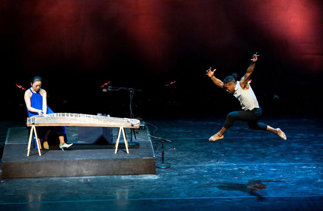 Un hombre da un salto de danza mientras una mujer toca un instrumento musical (Margaret Schulman)