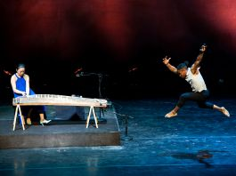 Homem salta enquanto mulher toca instrumento musical (Margaret Schulman)