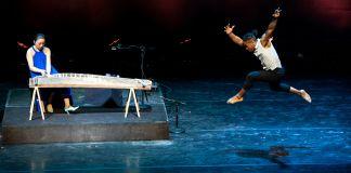 رجل يرقص وثبًا بينما تعزف امرأة على آلة موسيقية (Margot Schulman)