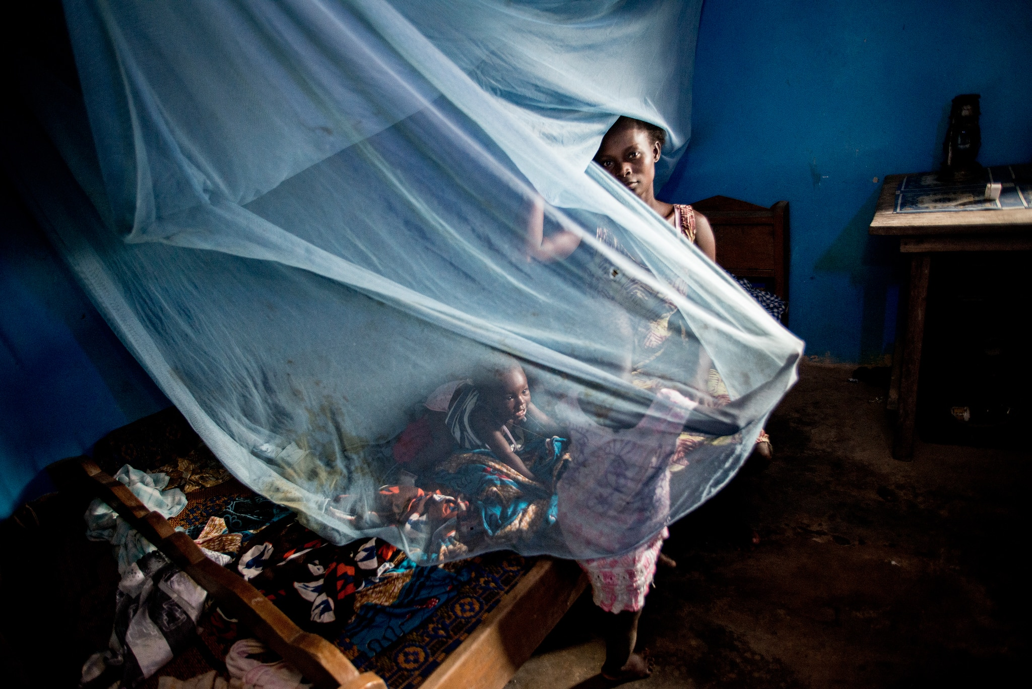 Woman with her family holding up mosquito net in a home (© K. Kasmauski/MCSP)