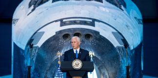 Le vice-président Mike Pence s'exprimant à un pupitre, une navette spatiale à l'arrière-plan (NASA)