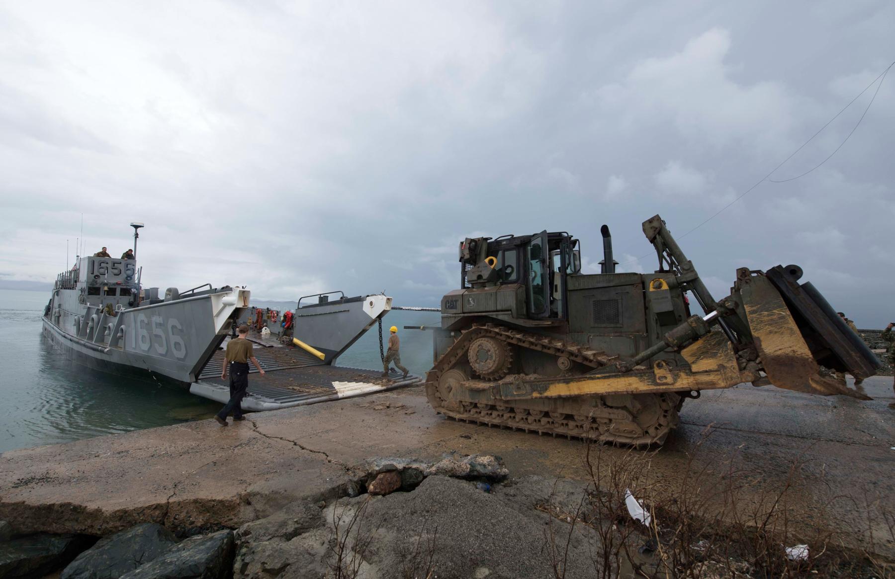 Landing Craft Utility offloading a bulldozer onto concrete pier (U.S. Navy)
