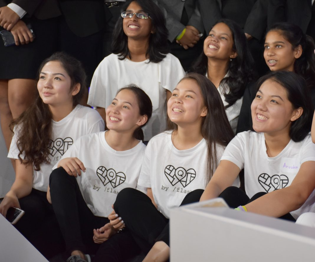 Teenage girls and a woman sitting and smiling at someone on a stage (Aziza Ibragimova/Almaty Maker Space)