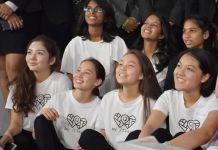 Adolescentes e mulher sentadas sorrindo para alguém em um palco (Aziza Ibragimova/Almaty Maker Space)