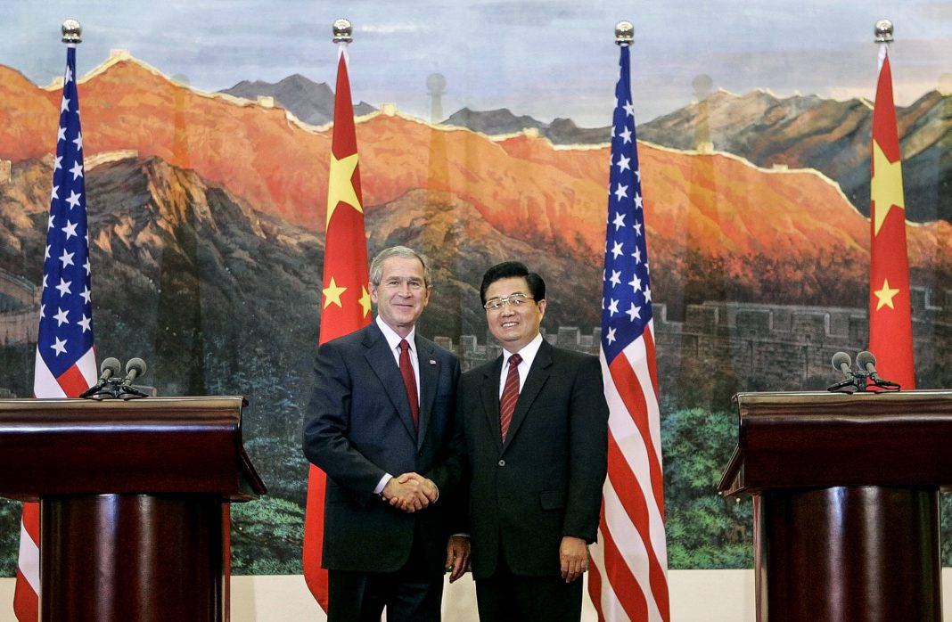 George W. Bush and Hu Jintao shaking hands in front of flags (© AP Images)