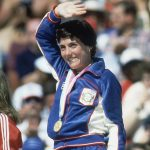 Joan Benoit, wearing medal and waving (© AP Images)